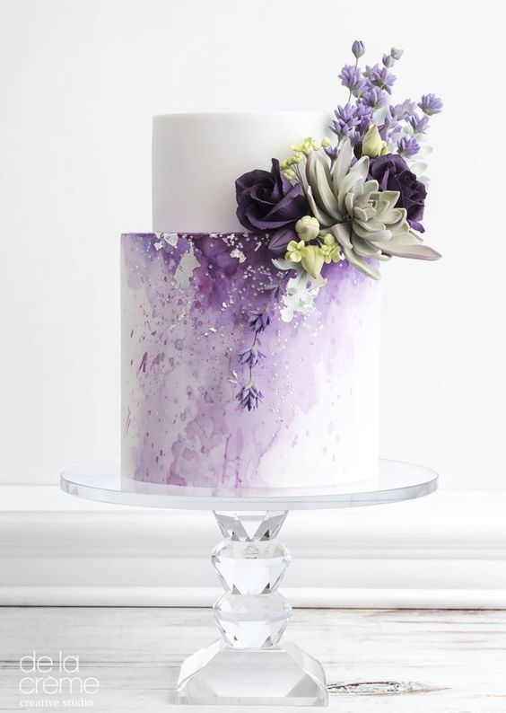 This image has an empty alt attribute; its file name is a-chic-lilac-wedding-cake-with-a-white-tier-an-ombre-effect-some-succulents-and-sugar-blooms.jpg